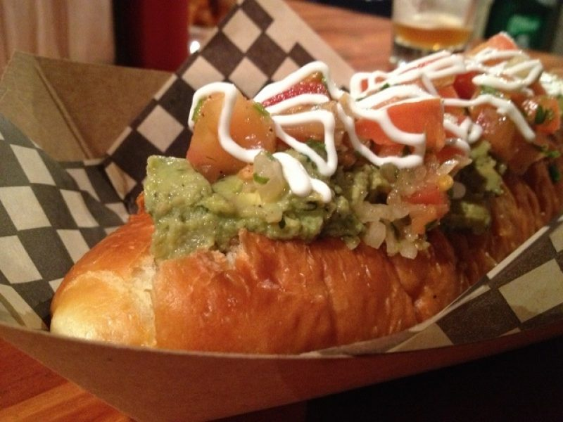 Hot dog in a paper tray with guacamole and tomatoes