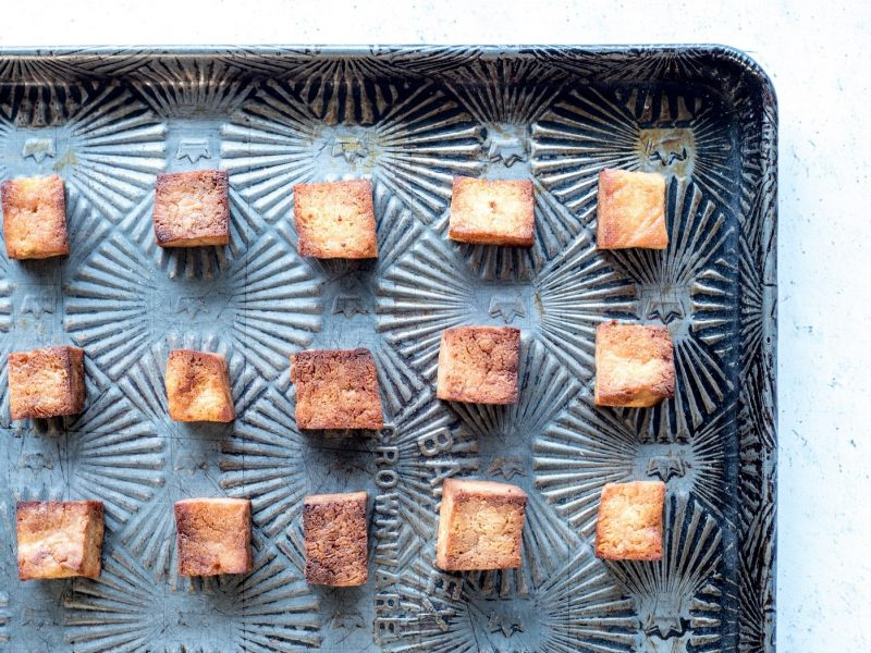 Top down view of a sheet pan covered with squares of baked tofu
