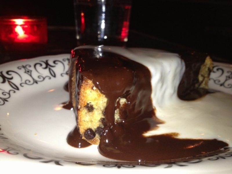 Piece of chocolate chip cake on a plate covered with chocolate sauce