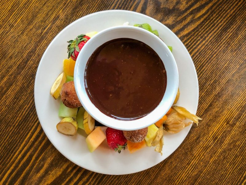 top down view of a plate of fruit with a bowl of chocolate fondue