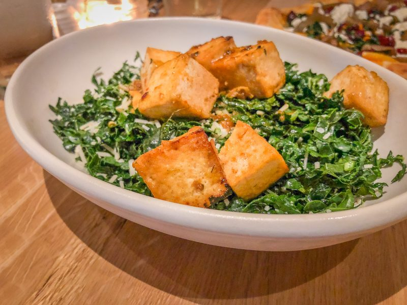 A round white bowl filled with kale and cubes of browned tofu