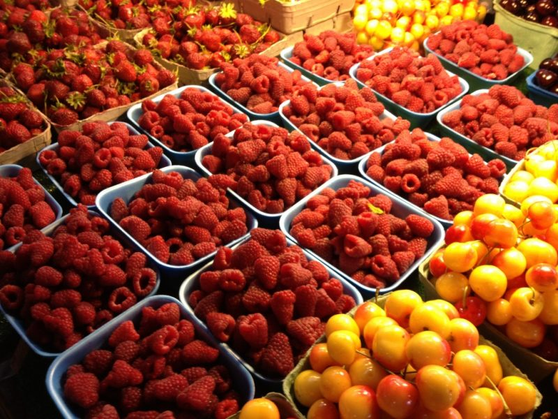 Baskets of cherries and raspberries at a produce stand